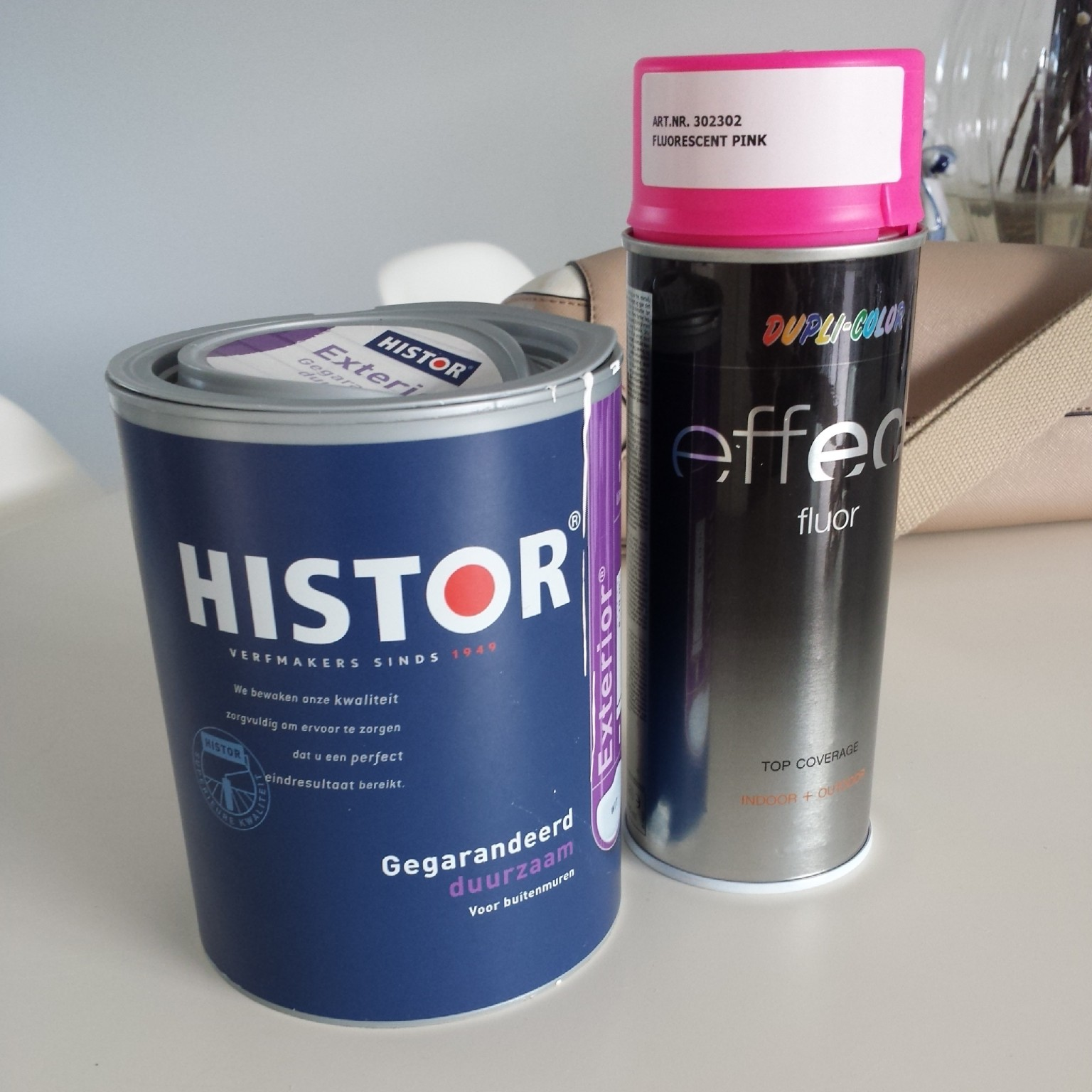 ... white exterior wall paint  and a neon pink spray can